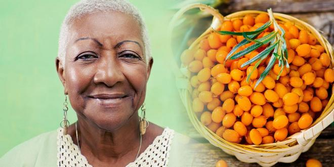 beautiful african american woman and a basket of sea buckthorn berries